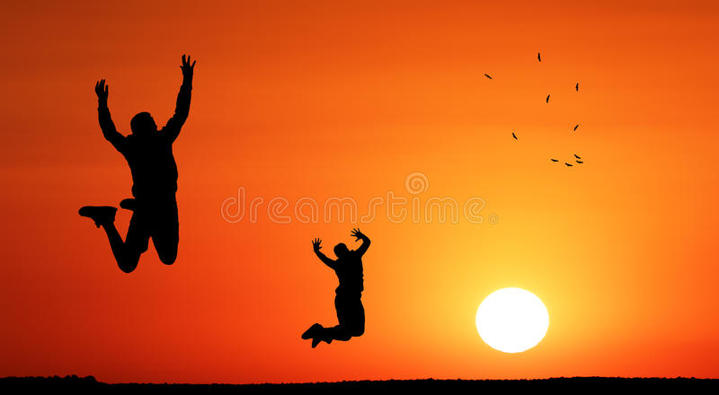 Teenager children jumping into the sunset towards freedom. Birds circling the sky represent the freedom they looking for. Conceptual art royalty free stock image