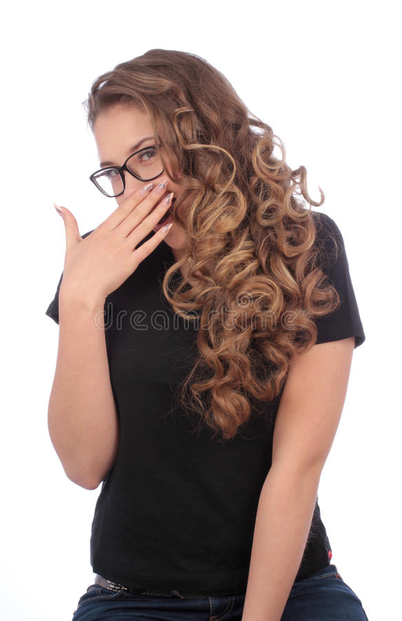 Teenager covering the mouth with her hand. Teenager with glasses covering the mouth with her hand on white background stock photo