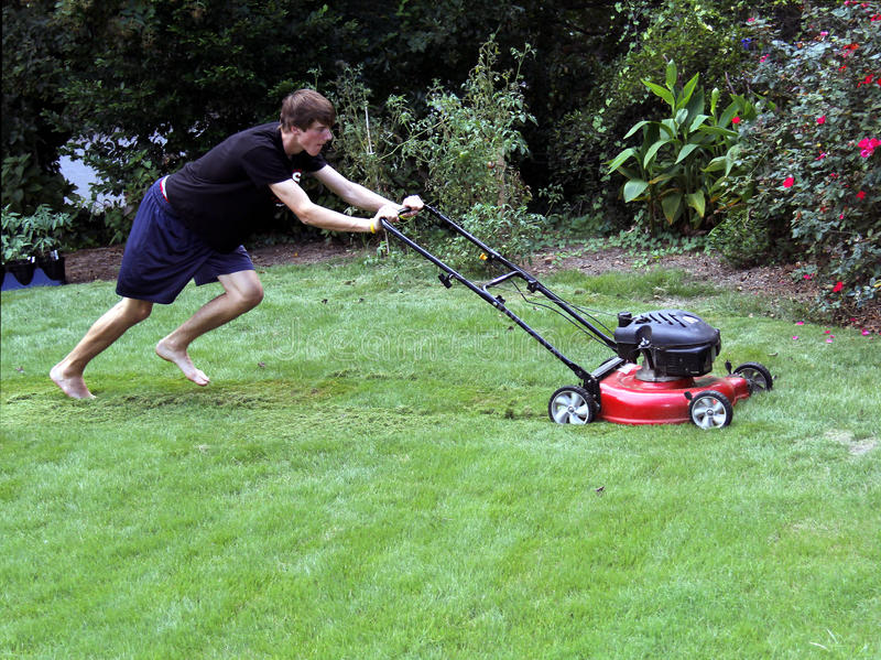 Teenager cutting grass. A teenager cutting the grass, pushing the lawnmower stock photos