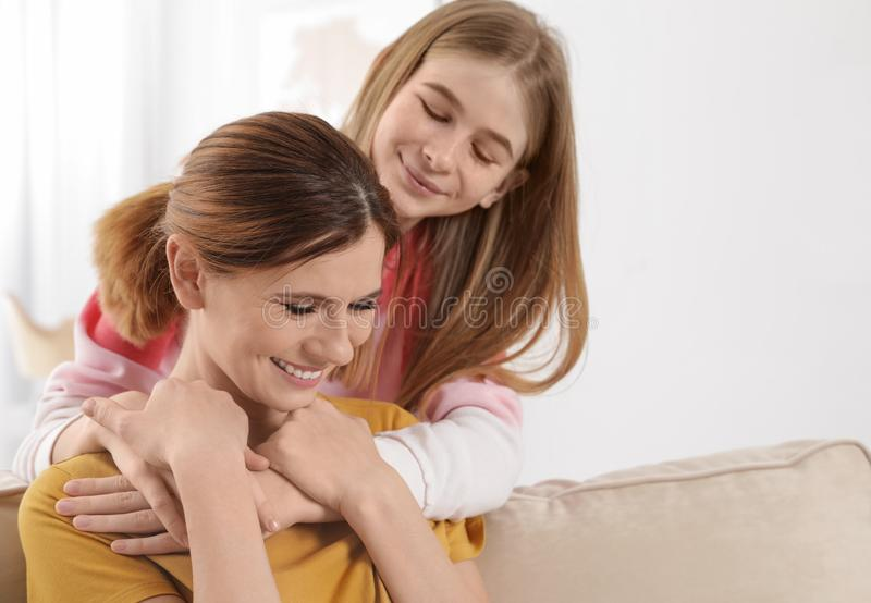 Teenager daughter hugging her mother. At home stock photos