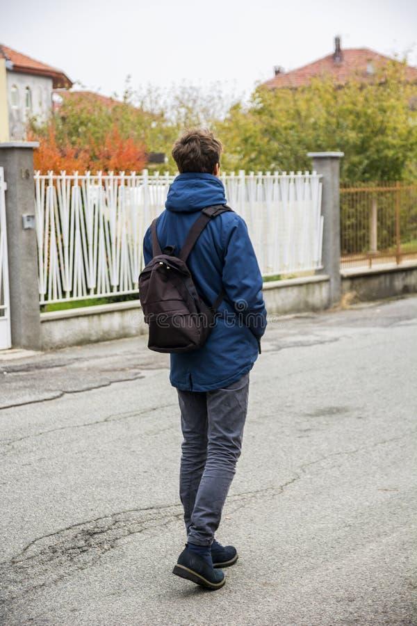 Teenager, der allein in Straße mit Rucksack geht lizenzfreie stockfotos