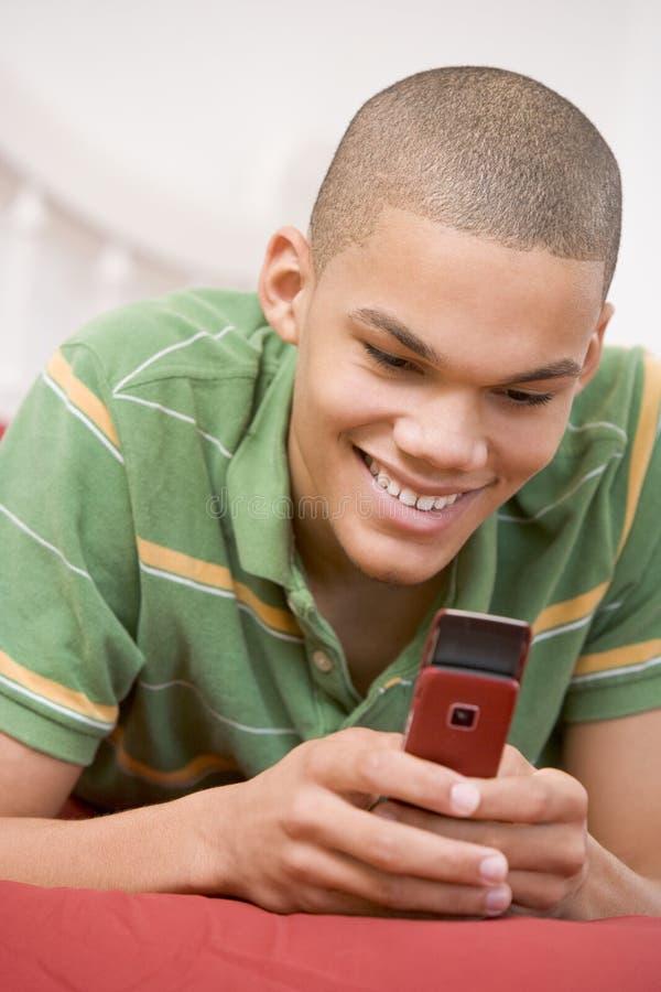 Teenager, der auf Bett unter Verwendung des Handys liegt lizenzfreie stockfotos
