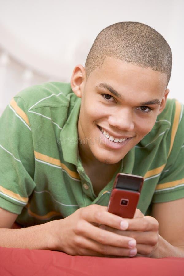 Teenager, der auf Bett unter Verwendung des Handys liegt stockbilder