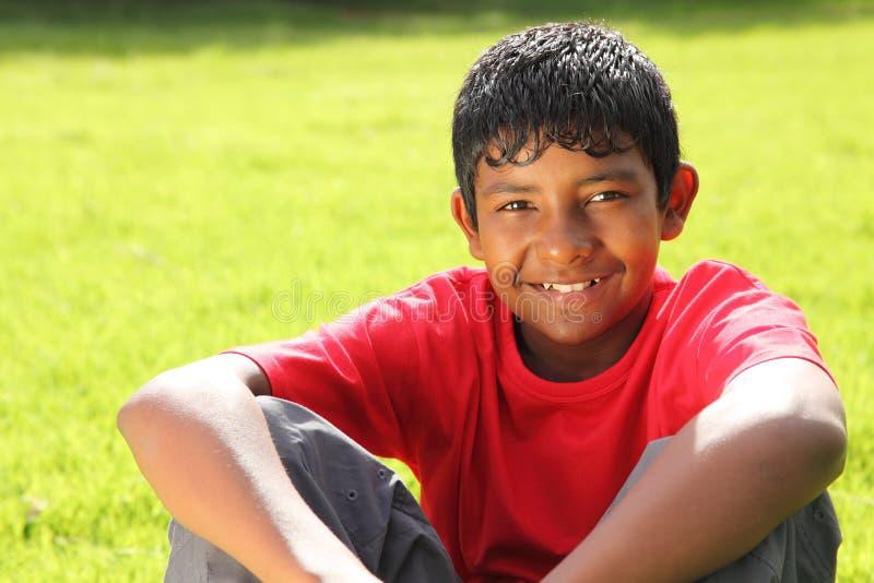 Teenager, der auf Gras im hellen Sonnenschein sitzt stockbilder