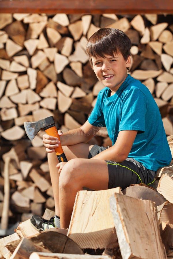 Teenager, der auf Haufen des Brennholzes sitzt stockfotos