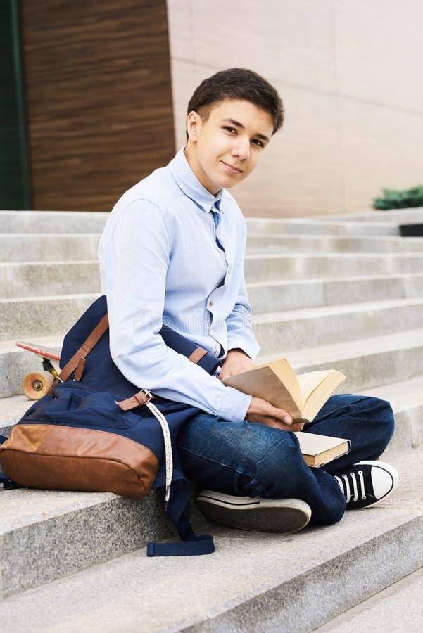 Teenager, der auf Schultreppe sitzt stockfotografie
