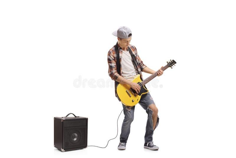Teenager, der die E-Gitarre angeschlossen an einen Verstärker spielt stockbild