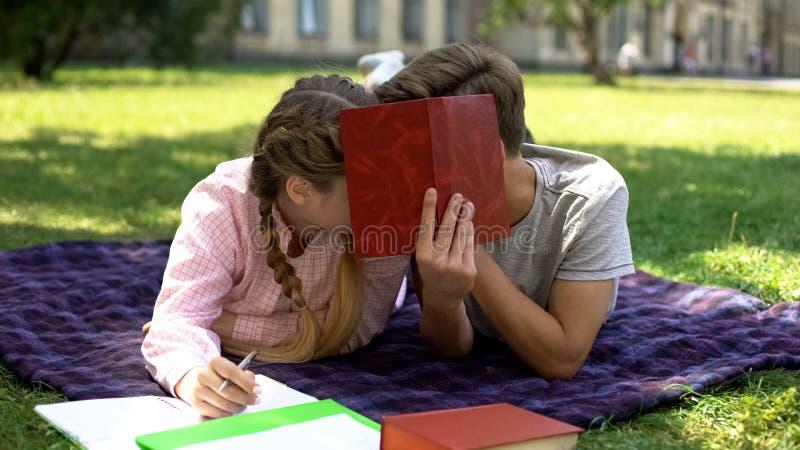 Teenager, der hinter dem Buch und K stockbild