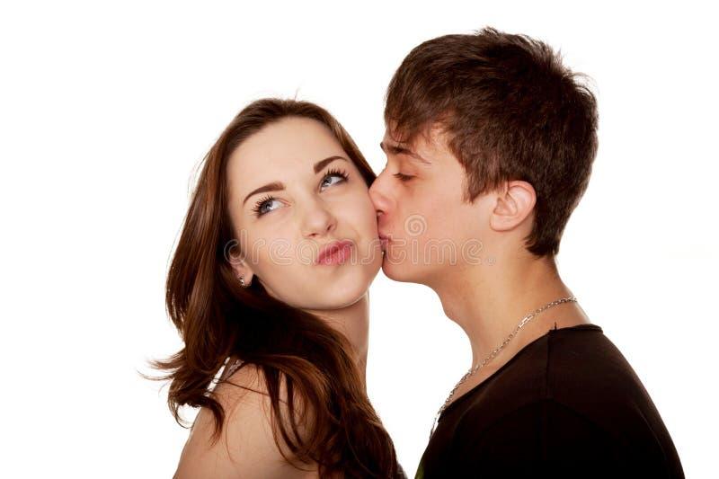 Teenager, der Mädchen küsst. Ein Gesicht verziehendes Mädchen lizenzfreies stockfoto