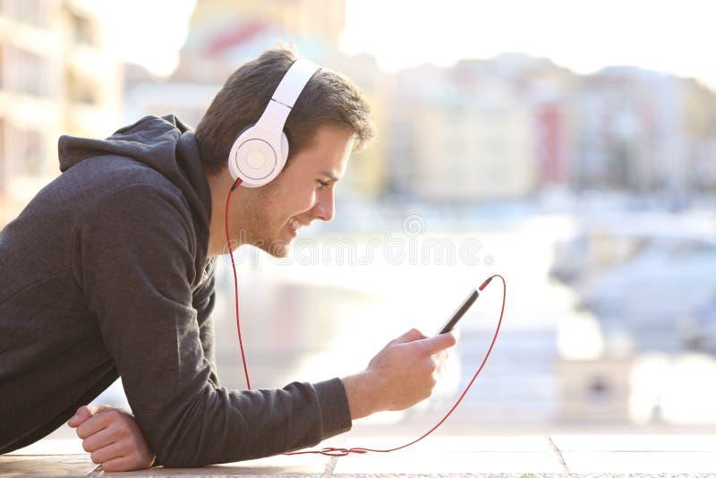 Teenager, der Musik mit Telefon und Kopfhörern hört stockbilder