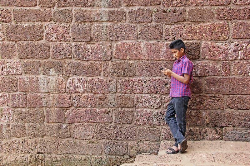 Teenager, der an Smartphone arbeitet stockbilder