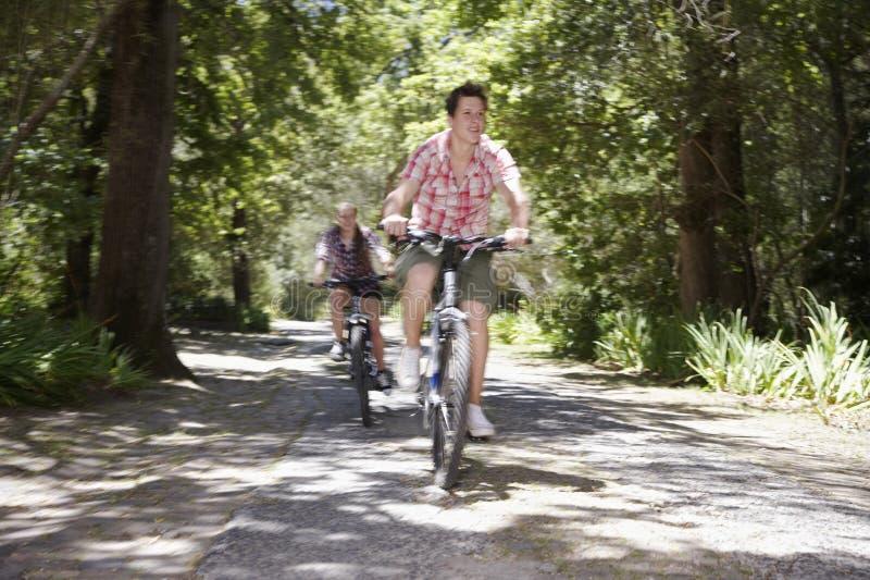 Teenager, die in Wald radfahren stockfotografie