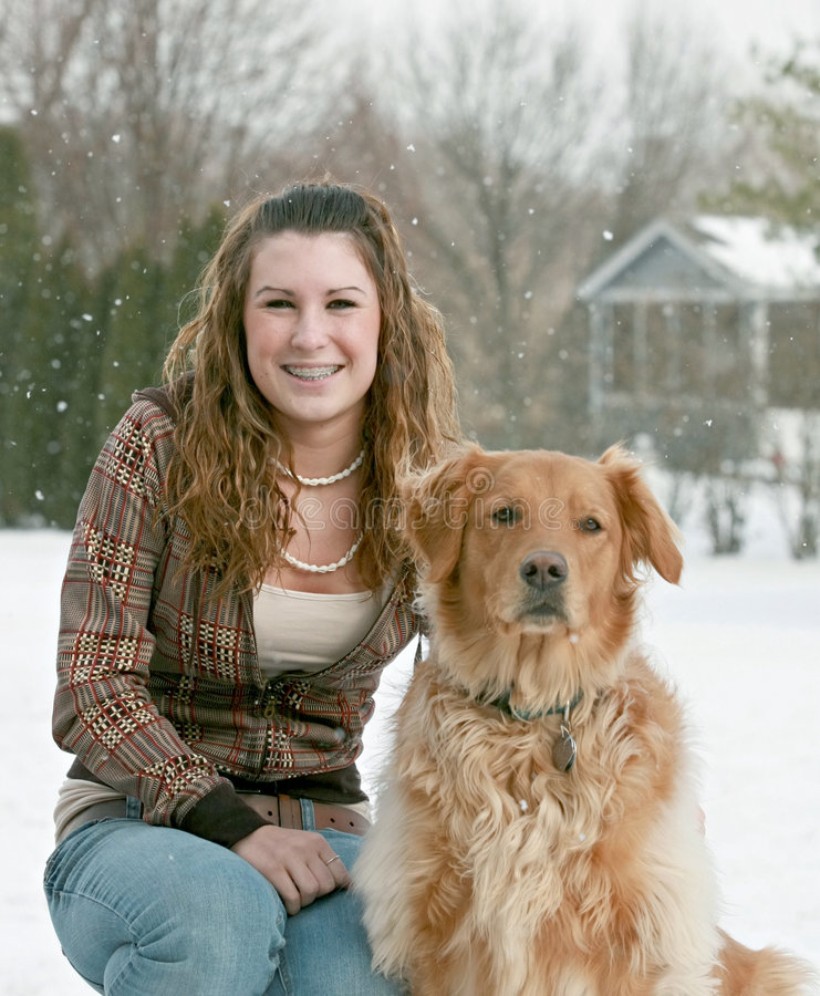 Teenager and Dog. Young Lady Smiling with Dog in a Snow Storm stock photography
