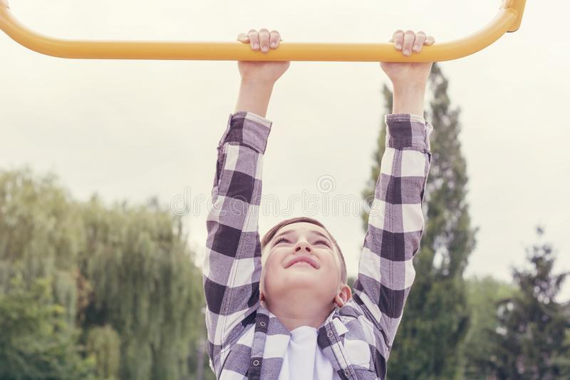 Teenager doing pull ups. Concentrated boy in plaid shirt doing exercise on horizontal bar outdoors. Healthy lifestyle concept. Blurred background royalty free stock photo