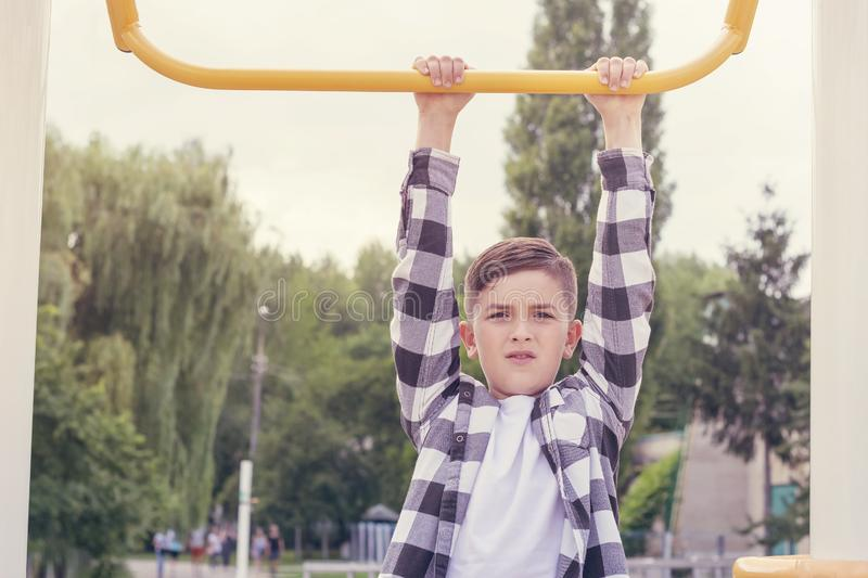 Teenager doing pull ups. Young boy doing exercise on horizontal bar outdoors. Healthy lifestyle concept. Blurred background royalty free stock images