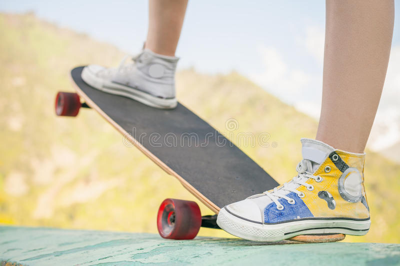Teenager doing a trick by skateboard outdoor at mountain. Close-up image of teenager doing a trick by skateboard - longboard on a street at the skate park stock images