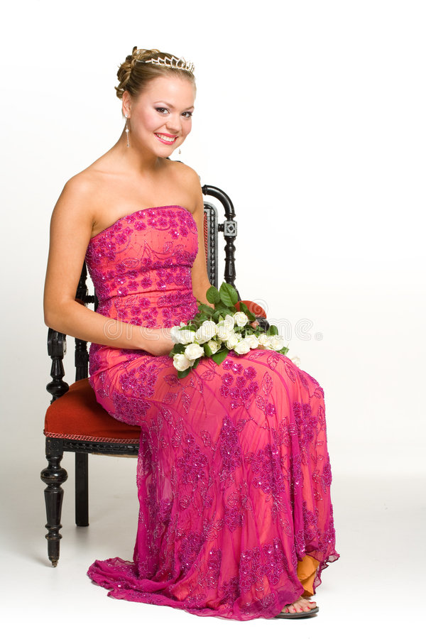 Teenager with dress and tiara. Happy female teenager in fashionable pink dress and tiara on chair with bouquet, isolated on white background royalty free stock photo
