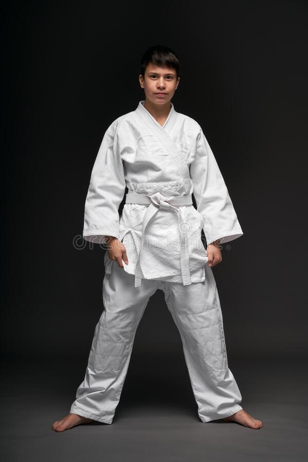 A teenager dressed in martial arts clothing poses on a dark gray background, a sports concept stock photos