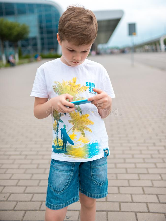 Teenager, dressed in white t-shirt, sits outdoor on skateboard and uses smartphone, digital gadget, plays computer games, browsin stock images