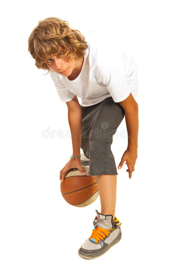 Teenager dribbling basketball. Teenager boy dribbling basketball isolated on white background royalty free stock images