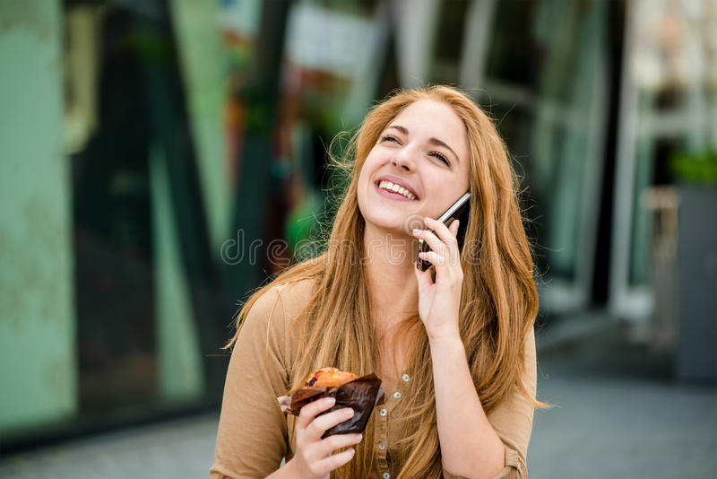Teenager eating muffin looking in phone royalty free stock photos