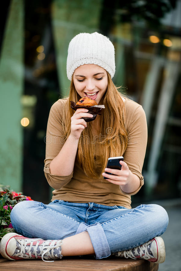 Teenager eating muffin looking in phone stock photography