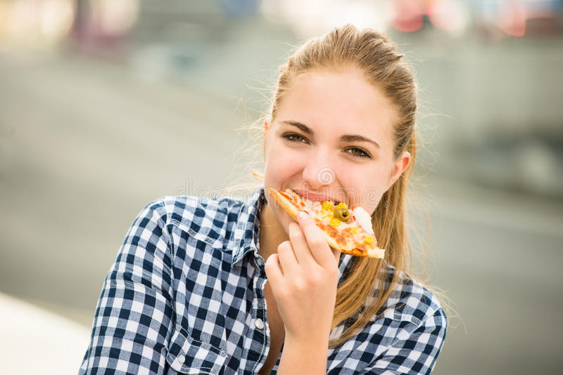 Teenager eating pizza in street stock photography
