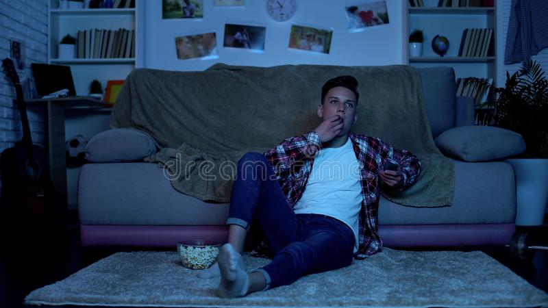 Teenager eating popcorn and switching channels on tv, wasting time, boredom. Stock photo royalty free stock photos