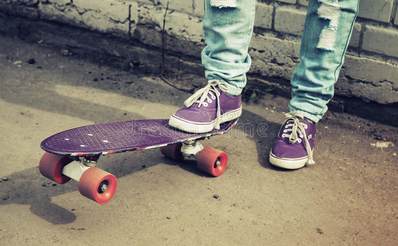 Teenager feet in jeans and gumshoes with skateboard royalty free stock image