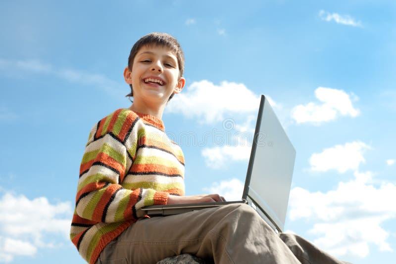 Teenager felice con un computer portatile fotografie stock libere da diritti
