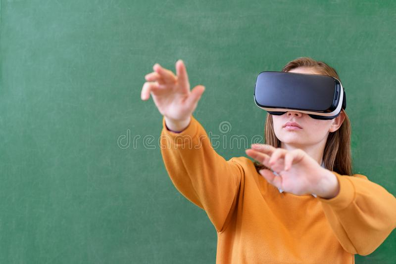 Teenager female student wearing virtual reality glasses in classroom at school. Innovative teaching methods. stock photo