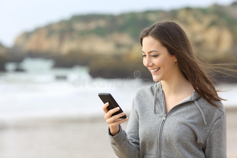 Teenager female texting in a smart phone. Happy teenager female texting messages or reading chat in a smart phone on the beach with the wind moving her hair stock image