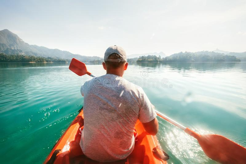 Teenager floating on kayak on calm water on Cheow Lan Lake, Khao Sok national park, Thailand royalty free stock images