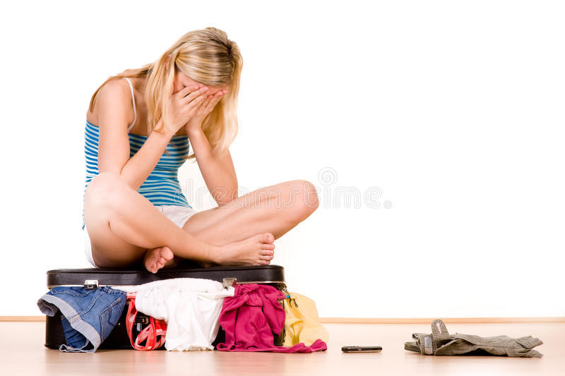 Teenager with full suitcase. Stressed teenager sat on top of over packed suitcase, white background royalty free stock photo