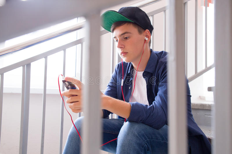 Teenager with gadget. Boy teenager playing with his gadget royalty free stock photos