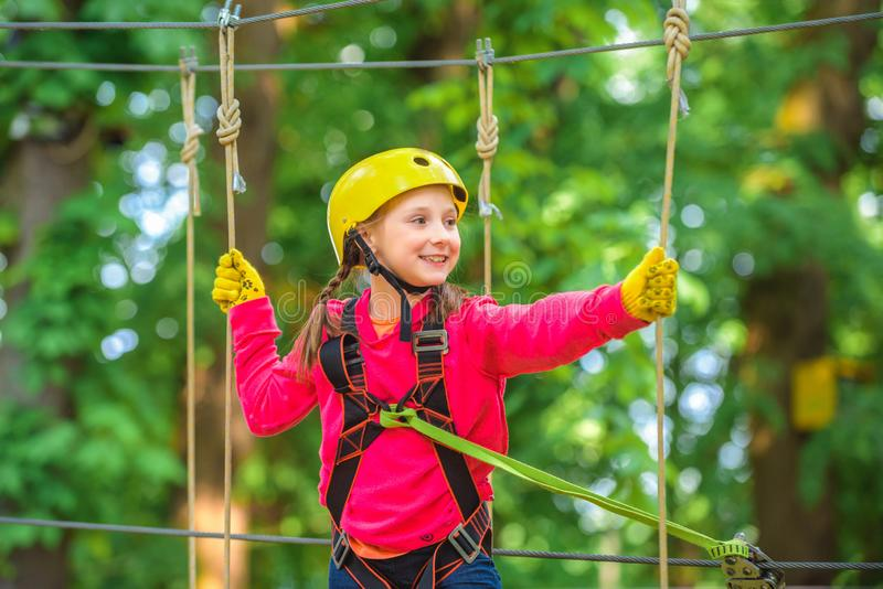 Teenager girl adventure and travel. Beautiful Little girl climbing and having fun in adventure Park. Happy little girl stock photo