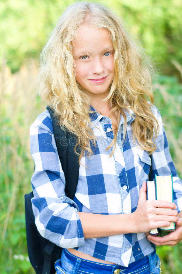 Teenager girl with backpack and books. Outdoor portrait of a beautiful teenager girl in casual clothes with backpack holding books royalty free stock photos