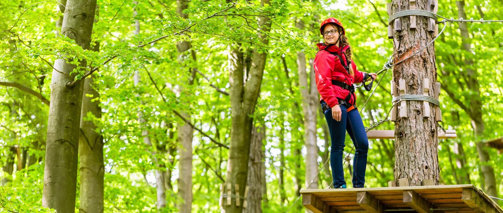 Teenager girl climbing in high rope course or parl stock photography