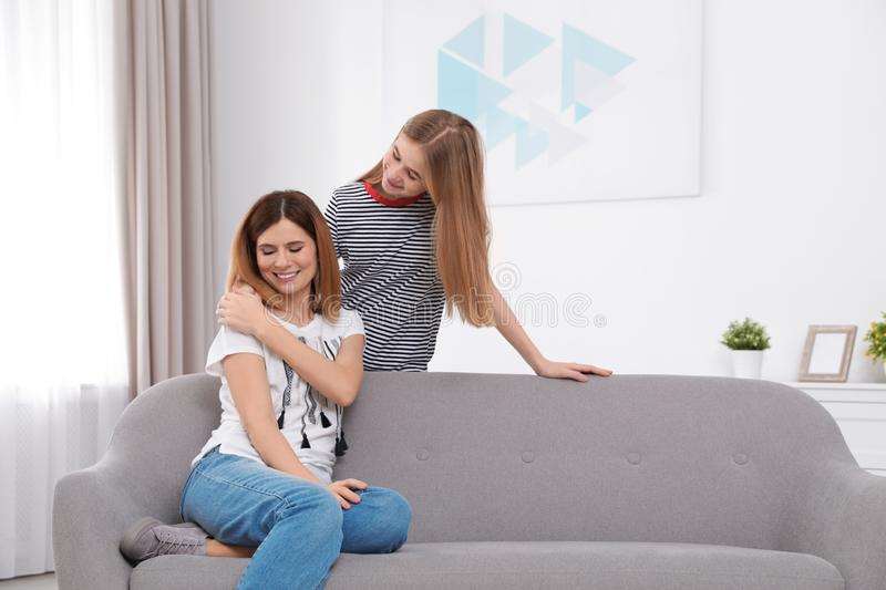 Teenager girl comforting her mother. At home royalty free stock photography