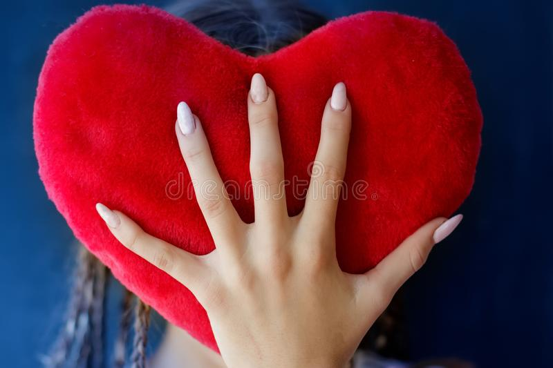 A teenager girl covers her face with a big plush heart. royalty free stock images