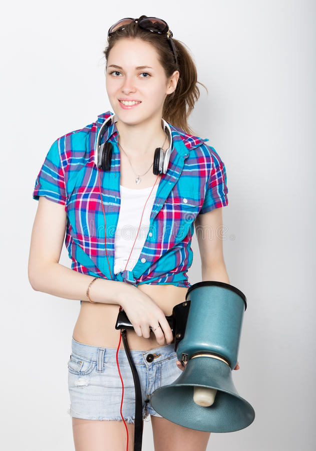Teenager girl in denim shorts and a plaid shirt express different emotions. counselor at a summer camp yelling through. Bullhorn royalty free stock photography