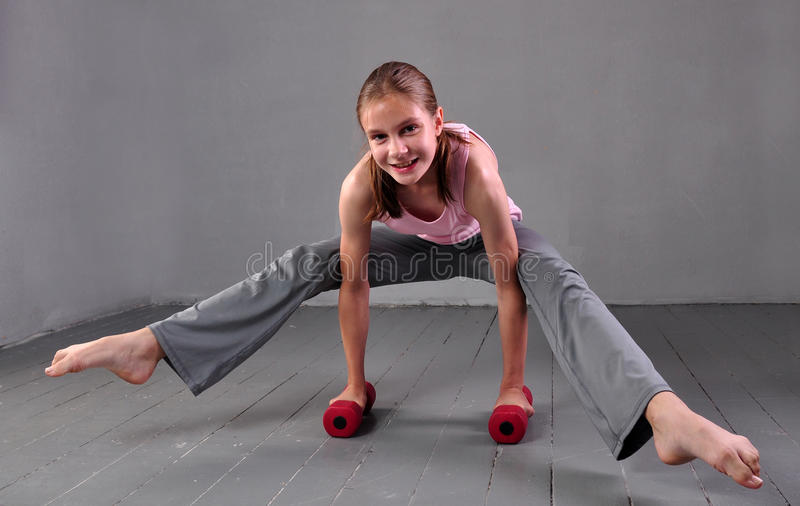 Teenager girl doing exercises with dumbbells to develop with dumbbells muscles on grey background. Full length portrait of teen ch stock image