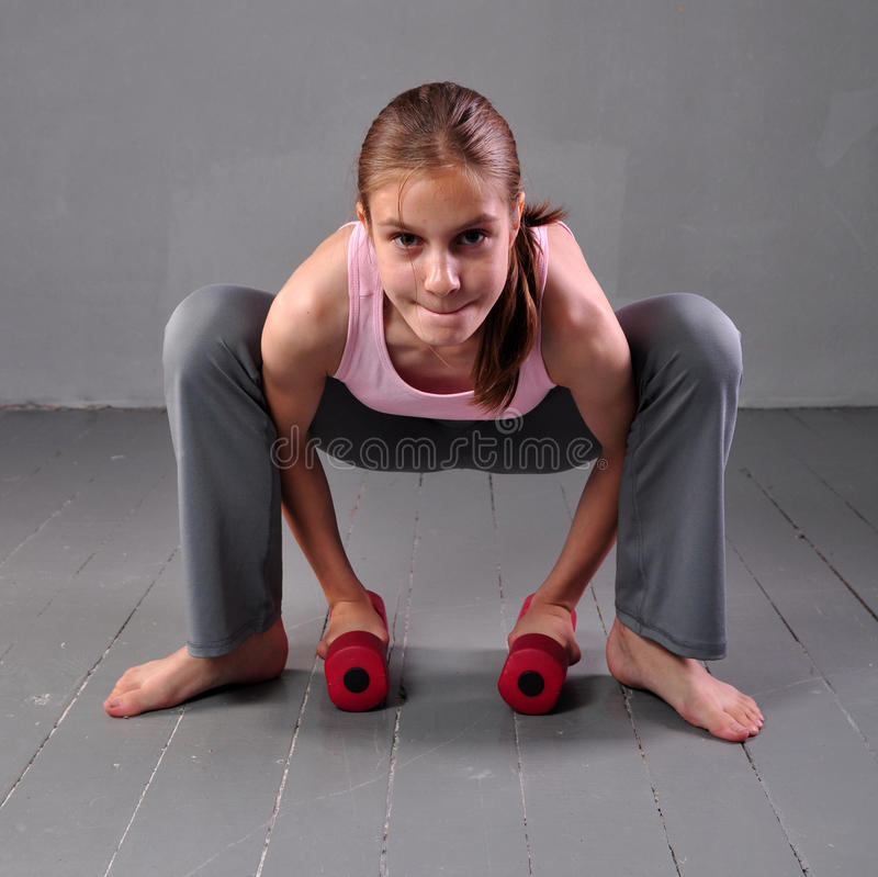 Teenager girl doing exercises with dumbbells to develop with dumbbells muscles on grey background. Full length portrait of teen ch stock images