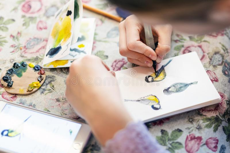 Teenager girl drawing bird in small paper drawing-pad. Close-up kid artist painting small picture on paper notepad with royalty free stock photos
