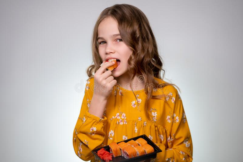A Teenager girl eating roll, sushi and sneezes. Japanese cuisine home delivery. Delicious. White background. Long hair, yellow dress stock photo
