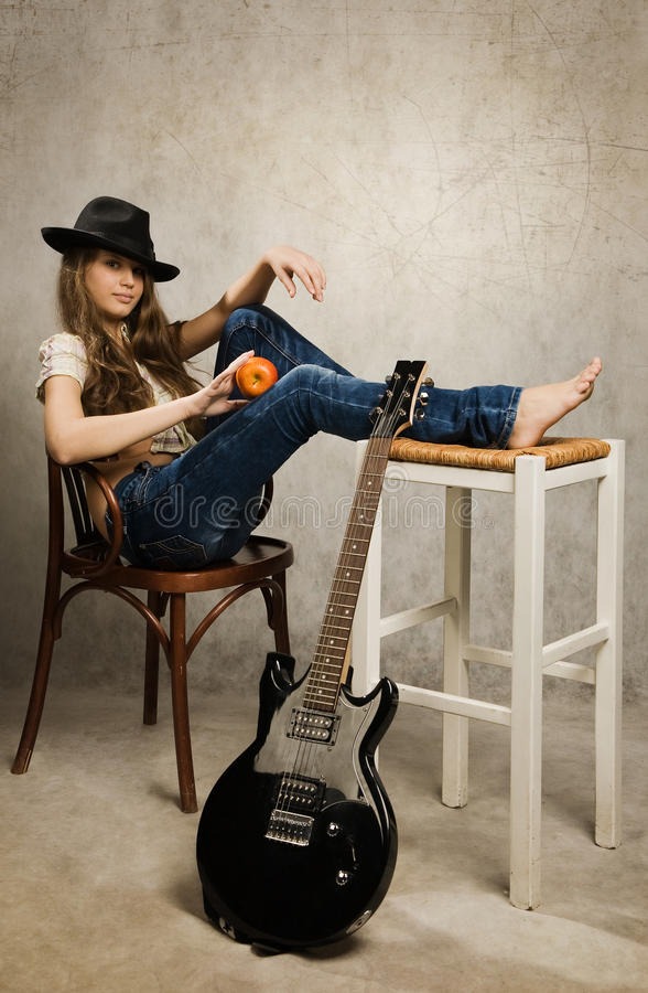 Teenager girl with electric guitar and apple royalty free stock photo