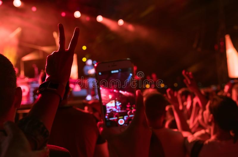 Teenager girl fan raised hand with V sign Gesture and shooting vertical video with smartphone popular band on the night concert. royalty free stock photo