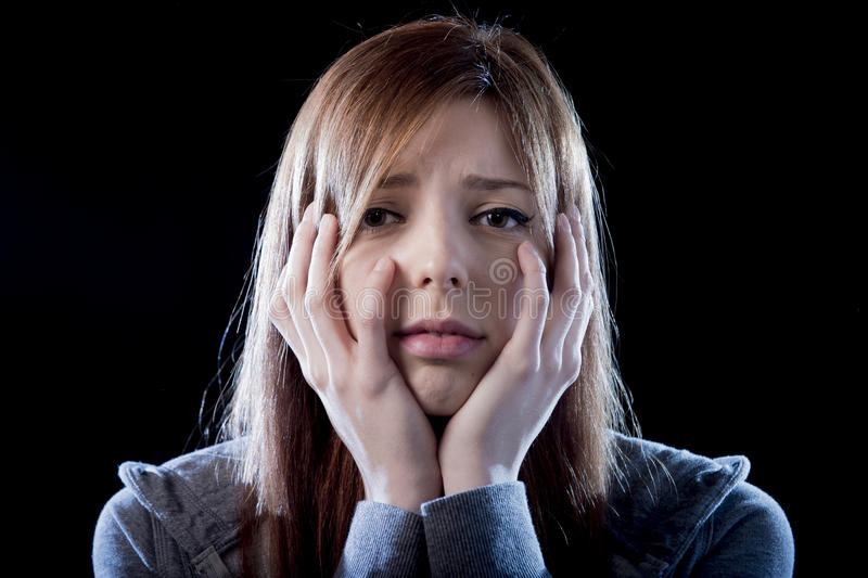 Teenager girl feeling lonely scared sad and desperate suffering depression bullying victim. Young beautiful teenager girl with red hair feeling lonely and scared royalty free stock photos
