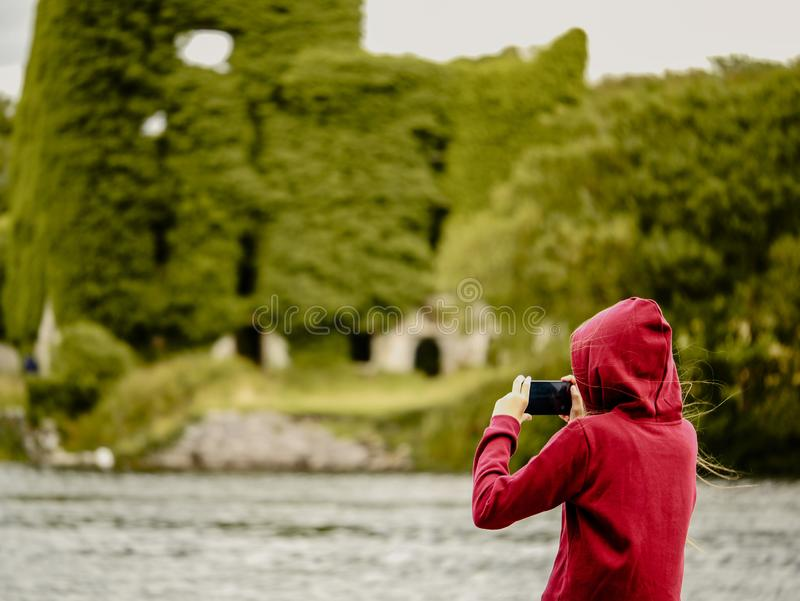 Teenager girl filming on her smart phone old castle and a river/ Selective focus. Menlo castle, Galway, Irleland. Concept: modern royalty free stock image