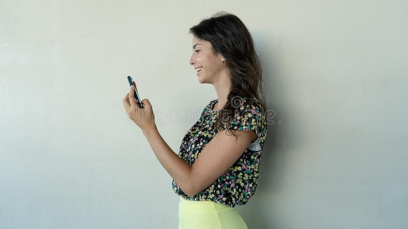 Teenager girl in flower dress looking screen cellphone, sharing in social media. Young lady touch cellular and flirting by chat stock photography